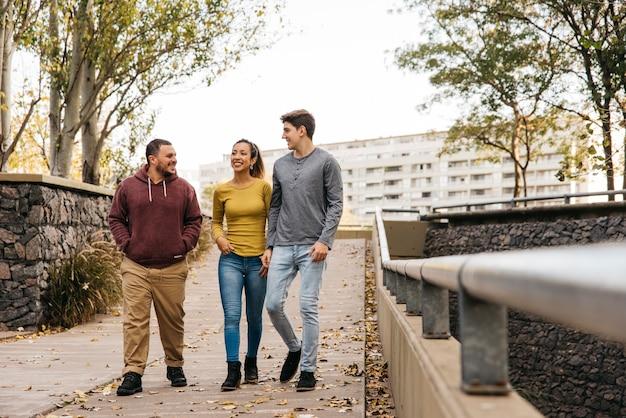 Multiethnic friends walking at autumn Free Photo