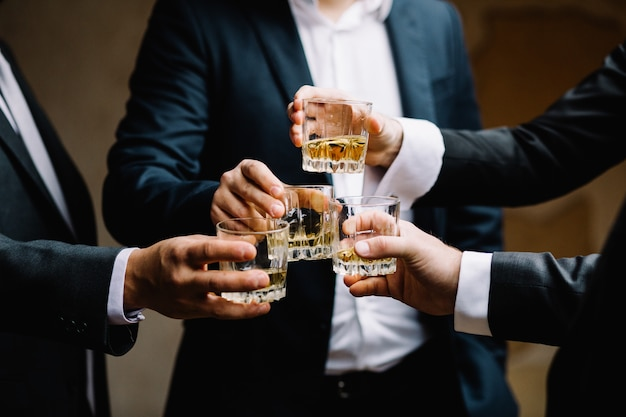 Multiethnic group of businessmen spending time together drinking whiskey and smoking Premium Photo