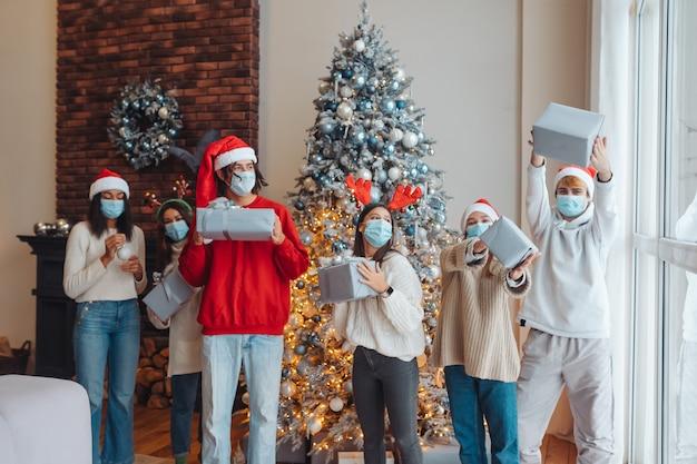 Gruppo multietnico di amici in cappelli di babbo natale con doni nelle mani. Foto Gratuite