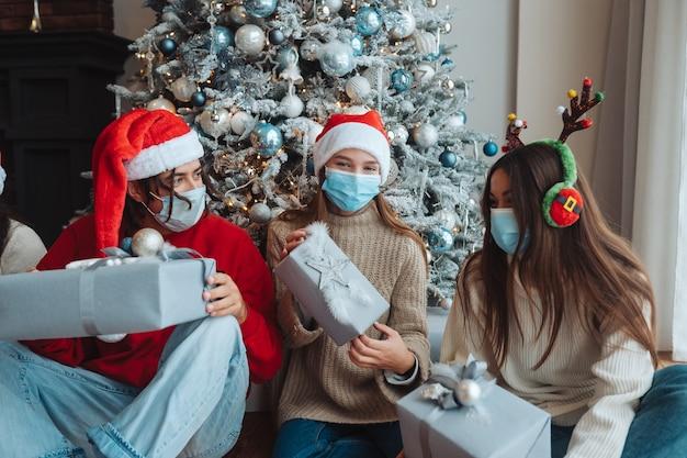 웃 고 손에 선물 카메라에 포즈 산타 모자에있는 친구의 다민족 그룹. 코로나 바이러스 제한에 따라 새해와 크리스마스를 축하하는 개념. 방역 휴가 무료 사진