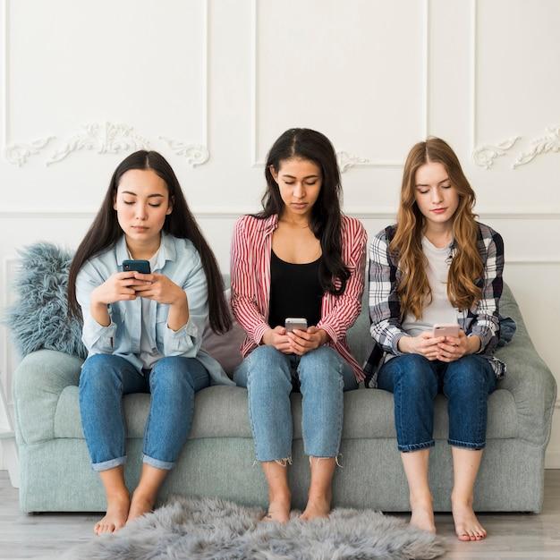 Multiethnic group of teenagers sitting using phones Free Photo