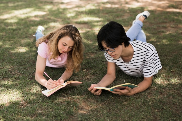 Multiethnic students on grass in park with books Free Photo