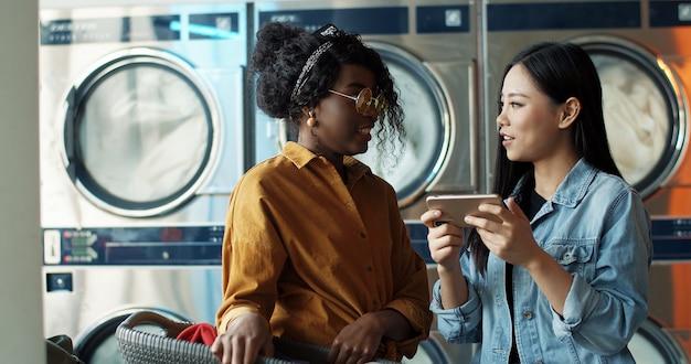 スマートフォンで話していると写真やビデオを見て多民族のスタイリッシュな若い女の子。ランドリーサービスで立っている友人。洗濯機が働いている間電話でアフリカ系アメリカ人とアジアの女性。 Premium写真