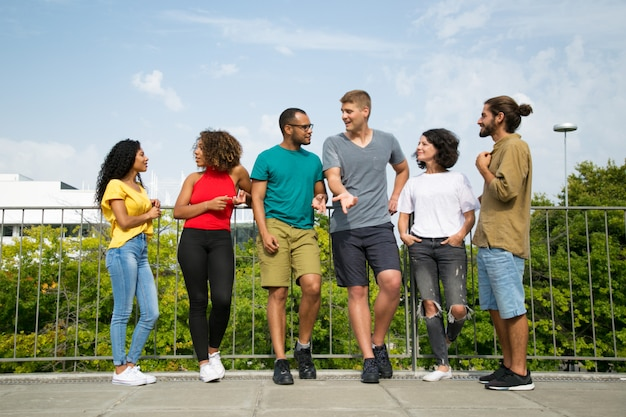 Multiethnic team of friends chatting on bridge Free Photo