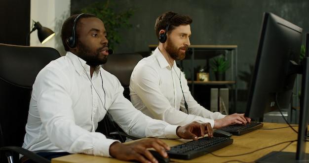 Многонациональные два молодых красивых оператора в гарнитурах работают за компьютерами и общаются с клиентами. Premium Фотографии