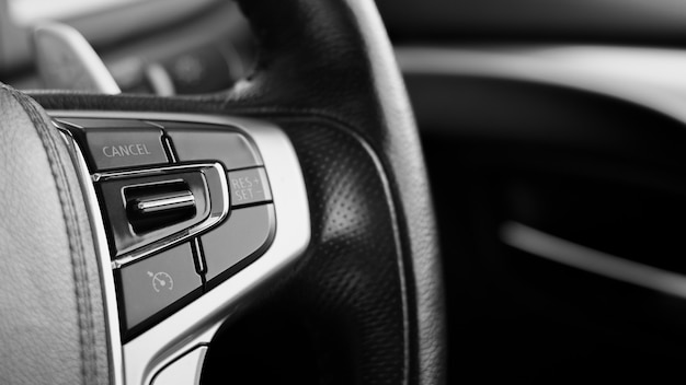 Multifunction buttons for quick control at a black steering wheel. Premium Photo