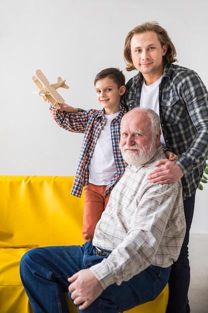 Multigenerational men hugging and looking at camera Free Photo