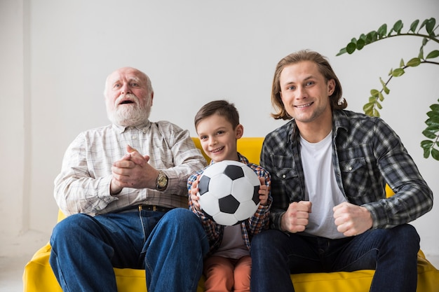 Multigenerational men watching soccer at home Free Photo