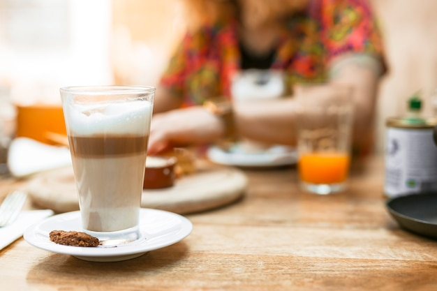 Multilayer coffee glass with cookie on saucer Free Photo
