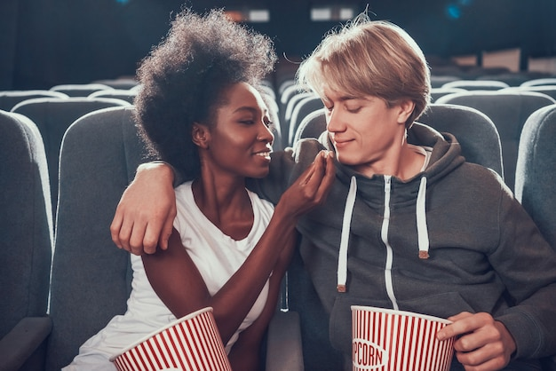 Multinational couple is feeding each other in cinema. Premium Photo