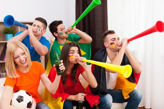 Многонациональные друзья дуют на вувузелу во время футбольного матча Бесплатные Фотографии