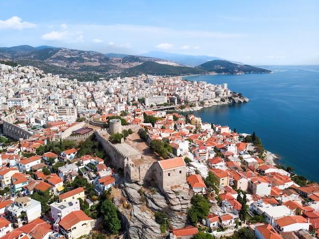 ギリシャ、カバラの背景にある複数の建物と砦、緑の丘 無料写真