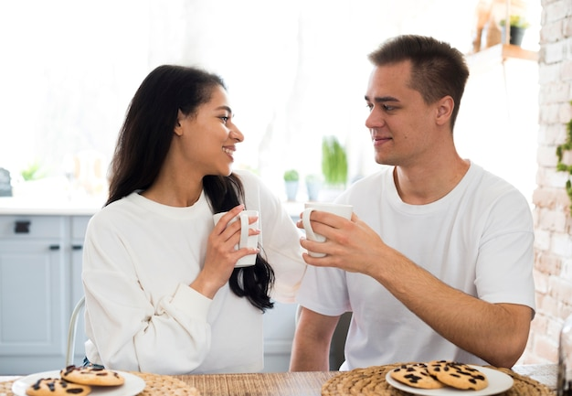 Multiracial couple drinking from cup at home Free Photo