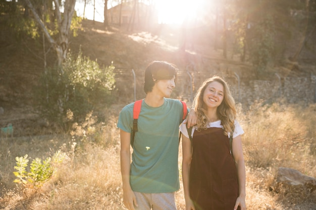 Multiracial couple standing against sunlight Free Photo