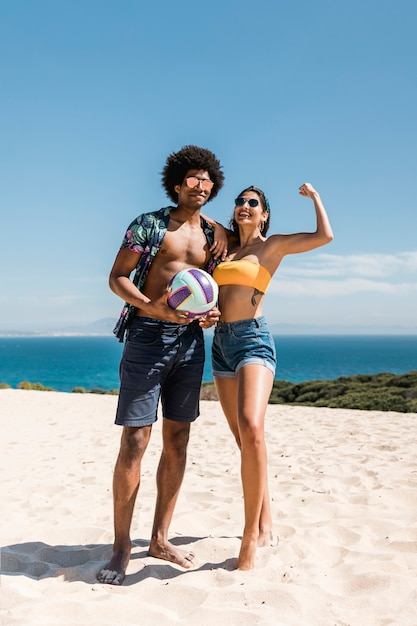 Multiracial couple with ball posing on beach Free Photo