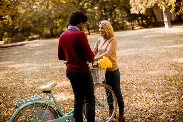 Multiracial couple with bicycle standing in the autumn park Premium Photo