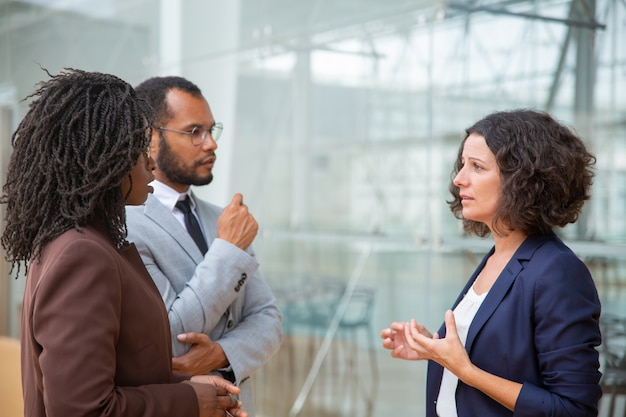 Multiracial coworkers talking Free Photo