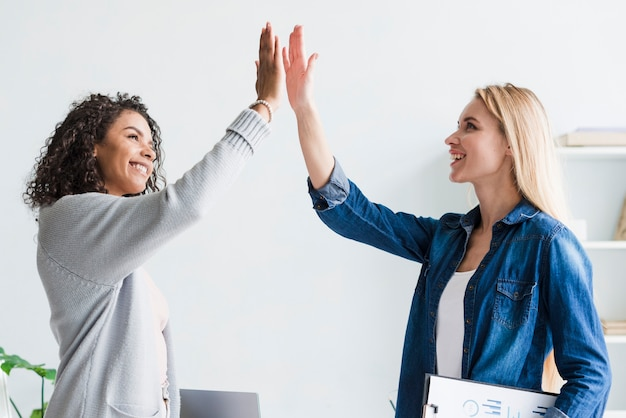 Multiracial employees giving high five at office Free Photo