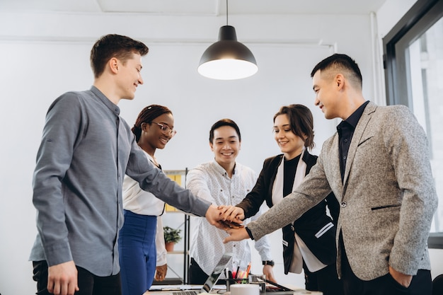 Multiracial euphoric business team people give high five at office table, happy excited diverse work group engaged in teambuilding celebrate corporate success win partnership power teamwork concept Premium Photo
