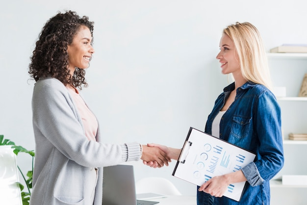 Multiracial female employees shaking hands in office Free Photo