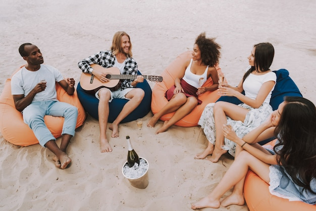 Multiracial friends playing music at beach party Premium Photo