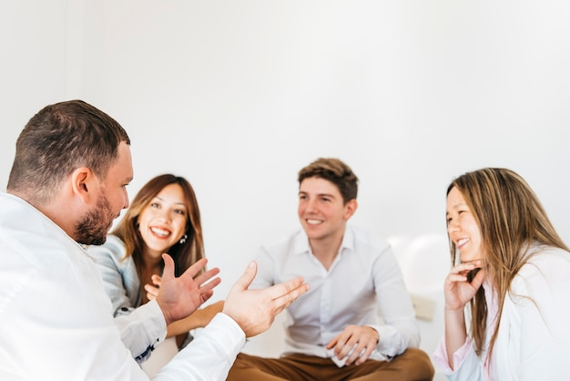 Multiracial group of coworkers listening to speaker Free Photo