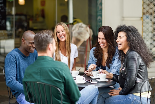 Multiracial group of five friends having a coffee together Free Photo