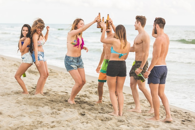 Multiracial group of friends having a party on the beach Premium Photo