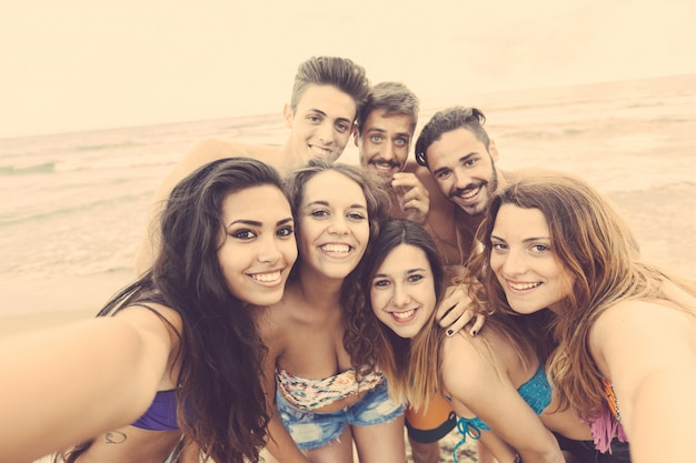 Multiracial group of friends taking selfie on the beach Premium Photo