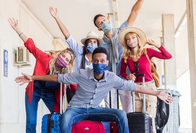 Multiracial group of friends at train station with luggage wearing  protective mask. Premium Photo