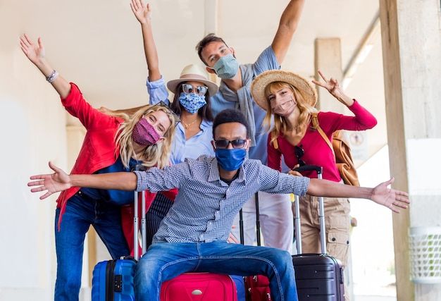 Multiracial group of friends at train station with luggage wearing  protective mask Premium Photo