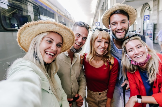 Multiracial group of friends wearing face mask taking a selfie at train station. travel, holiday and vacation new normal concept Premium Photo