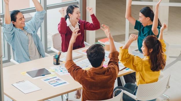 オフィスでのブレーンストーミング会議でビジネスジェスチャーハンドハイファイブを話し合って笑ったり笑ったりするスマートカジュアルウエアの若い創造的な人々の多民族グループ。同僚のチームワークの概念。 無料写真