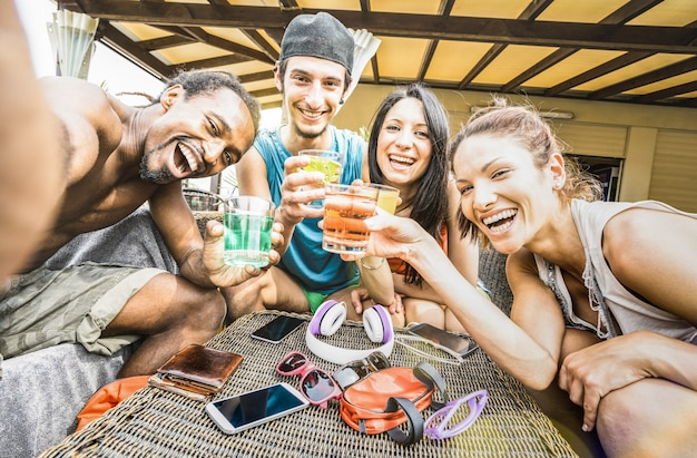 Multiracial happy friends group taking selfie and having fun drinking cocktails at beach Premium Photo