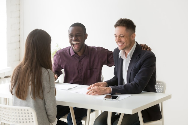 Multiracial hr managers laughing at funny joke interviewing woman applicant Free Photo