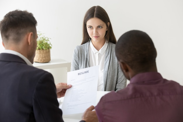 Multiracial hr reading resume of millennial job applicant at interview Free Photo