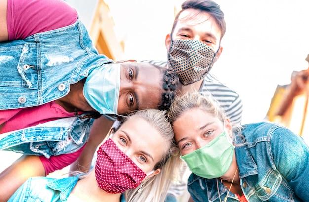 Multiracial millenial friends taking selfie smiling behind face masks Premium Photo