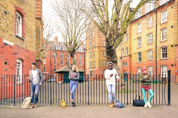 Multiracial people group and urban friends using smartphone near shoreditch london Premium Photo
