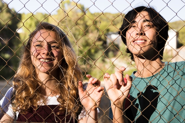Multiracial young couple touching chain link Free Photo