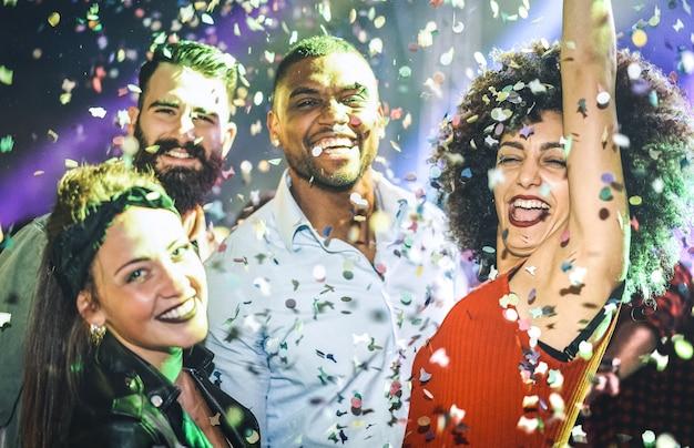 Multiracial young friends dancing at night club under confetti rain Premium Photo