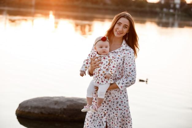 Мама, маленькая дочь на улице. молодая мать с ребенком женщина ходить на пляж возле озера на закате. семейный отдых на пруду. портрет мамы с ребенком вместе в природе. Premium Фотографии