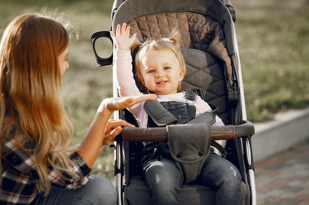 街の通りのお母さん。乳母車に座っている彼女の幼児を持つ女性。家族の概念。 無料写真