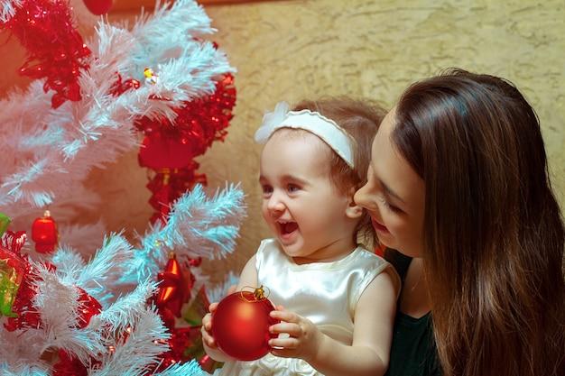 Мама с маленькой дочкой украшают елку и веселятся Premium Фотографии