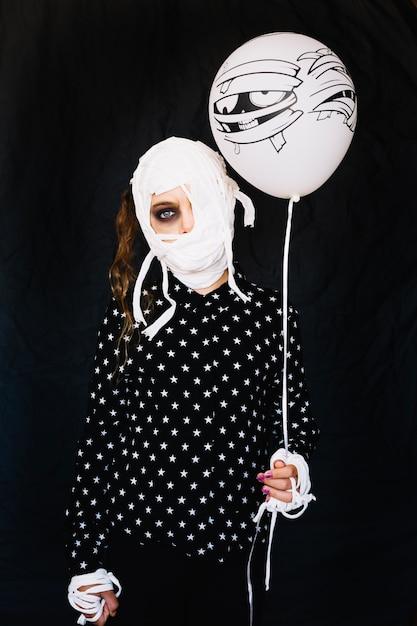 Mummy girl with bandages holding balloon Free Photo