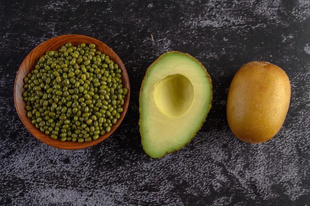 Бобы мунг, авокадо и киви на черном цементном полу. Бесплатные Фотографии