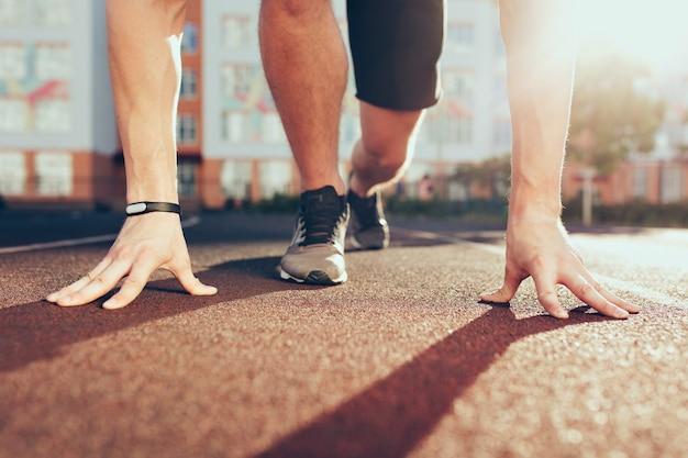 아침에 경기장에 강한 남자의 운동화에 근육, 손, 햇빛, 다리. 그는 시작할 준비가되어 있습니다. 무료 사진