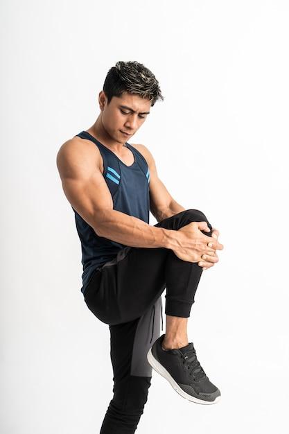 측면을 향한 운동복을 입은 근육 남자는 배 앞에서 다리를 들어 다리 스트레칭을합니다. 프리미엄 사진