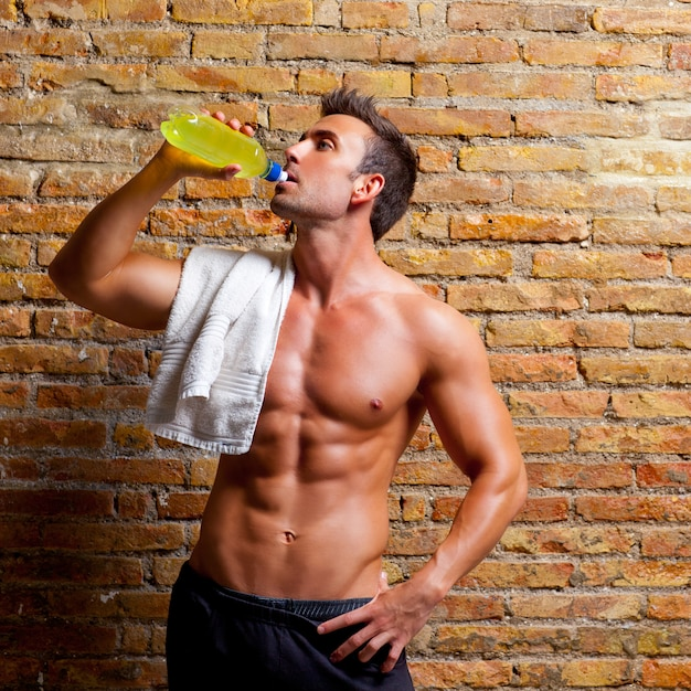 Muscle shaped man at gym relaxed drinking Premium Photo