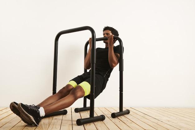 흰 벽과 가벼운 나무 바닥에 모바일 바에 체중 행을하는 검은 운동 장비에 근육 아프리카 계 미국인 선수. 무료 사진