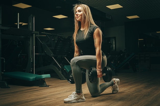Muscular attractive woman in gym lifting dumbbells Premium Photo